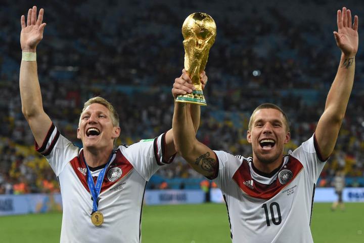 Bastian Schweinsteiger und Lukas Podolski jubeln mit dem WM-Pokal nach dem Finale der Fußball-WM 2014 zwischen Deutschland und Argentinien.