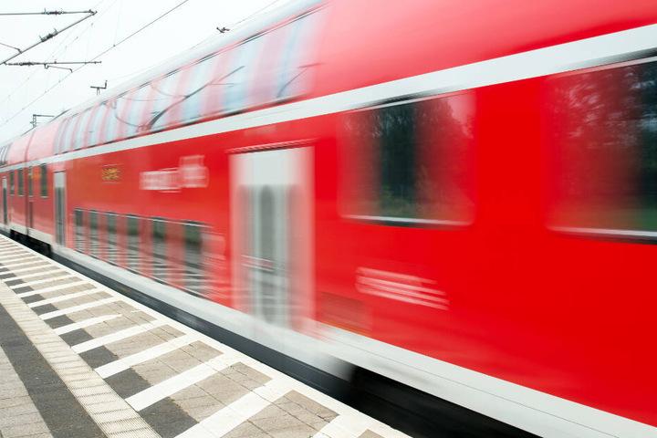 Ein Regionalexpress fährt an einem Bahnhof los.