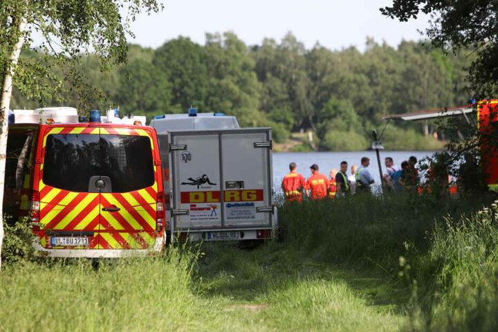 Zahlreiche Einsatzkräfte von Feuerwehr und DLRG suchen am und im See nach dem Schwimmer.