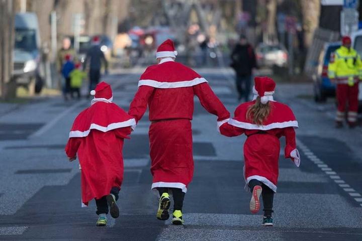 Drei Nikoläuse aus zwei Generationen laufen auf der 2,5 Kilometer langen Strecke dem Ziel entgegen.