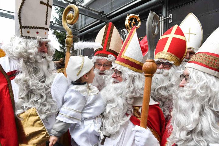 Sechs Nikoläuse stehen nach einem Gottesdienst vor der katholischen Kirche in Friedrichshafen-Jettenhausen.