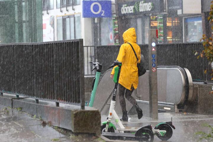Bei starkem Regen geht eine Frau in Hamburg in eine Unterführung.