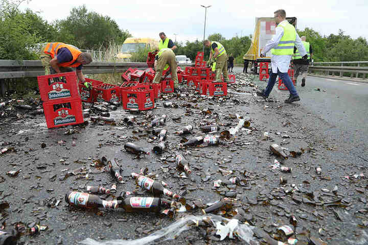 Mehrere Helfer befreien die Straße von dem Bier.