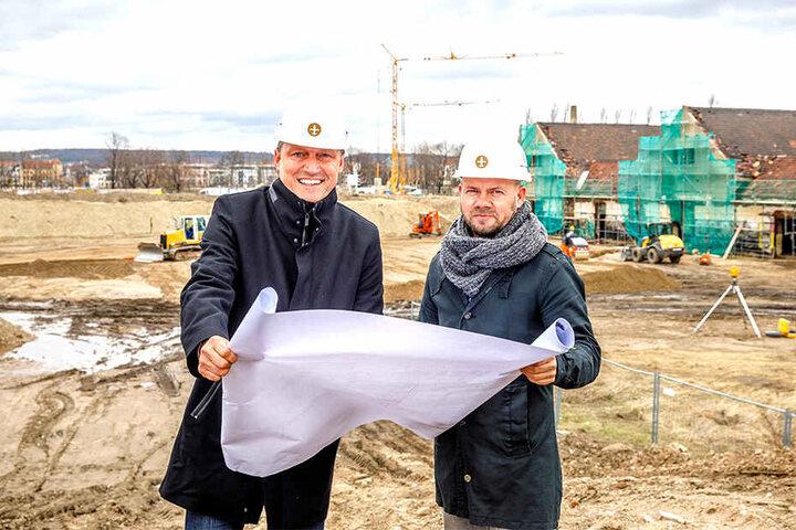 """Mirco Meinel (47, l.) und sein Projektleiter Jörg Ullrich (48) schauen auf den Bauplan. Direkt hinter ihnen wird der """"Ostra-Dome"""" entstehen. Rechts im Foto: die künftigen """"Ostra-Studios""""."""