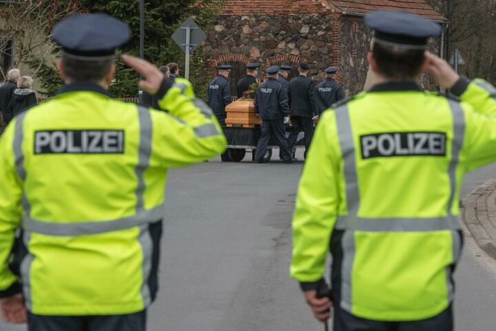 Zwei Polizisten salutieren bei der Beerdigung ihre von Jan G. im Einsatz getöteten Polizisten.