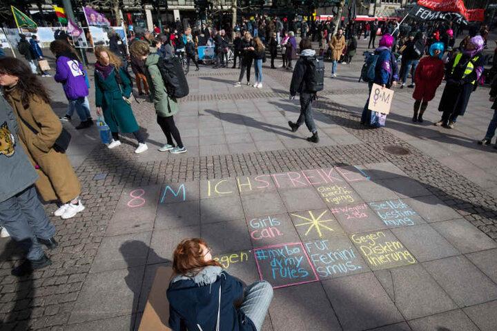Am Rathausmarkt schreiben Frauen ihre Botschaften mit Kreide auf den Boden.
