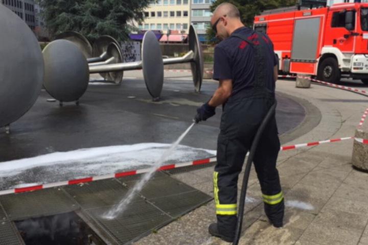 Die Feuerwehr spült den Restschaum im Brunnen weg.