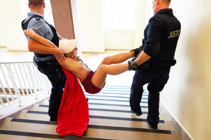 Das Foto zeigt eine der beiden Frauen, wie sie von den Justizbeamten fortgetragen wird.