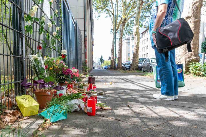 Am Tatort, an dem eine 36-jährige Frau erstochen wurde, liegen Blumen und Kerzen.
