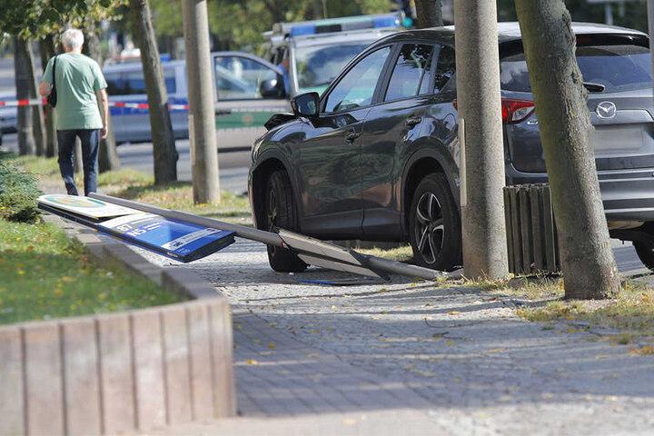 """Nach dem Unfall steht der beschädigte Mazda SUV an der Haltestelle """"Wiederitzscher Landstraße"""" neben dem herausgerissenen Haltestellenschild."""