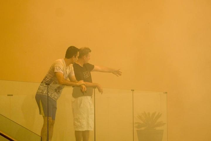 Einwohner stehen vor einem Haus im rötlichen Rauch eines Buschfeuers.