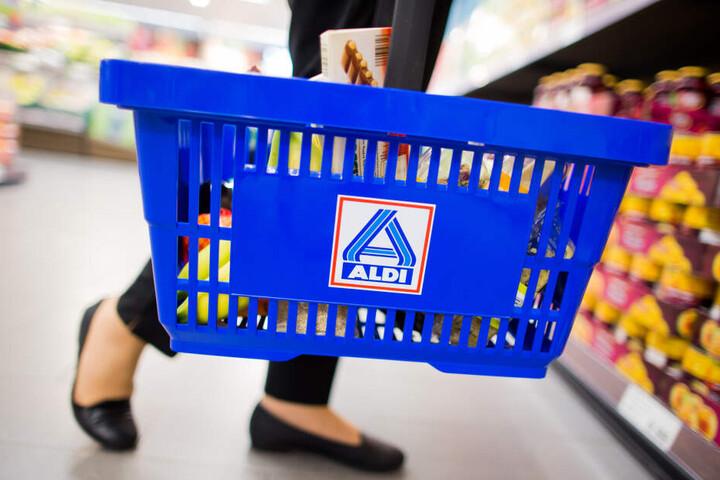 Eine Frau hält einen Einkaufskorb von ALDI in der Hand.