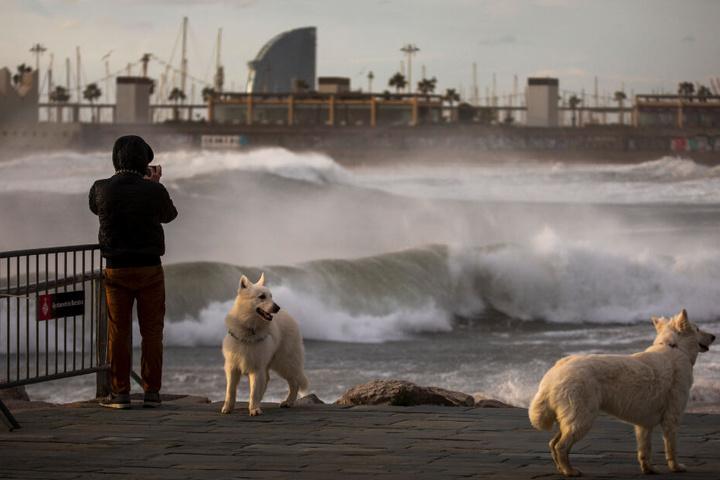 Ein Mann fotografiert das Mittelmeer bei starkem Wind in Barcelona.
