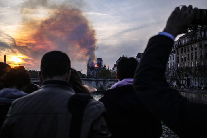 Zahlreiche Menschen sehen sich die Brennende Kathedrale Notre-Dame an.