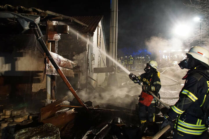 Zwei Feuerwehrkräfte löschen das Gebäude neben einer Sammelunterkunft.