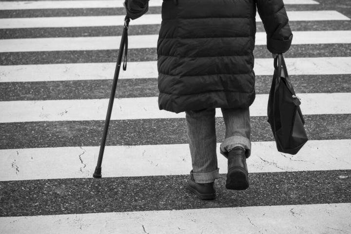 Eine Seniorin überquert eine Straße (Symbolbild).
