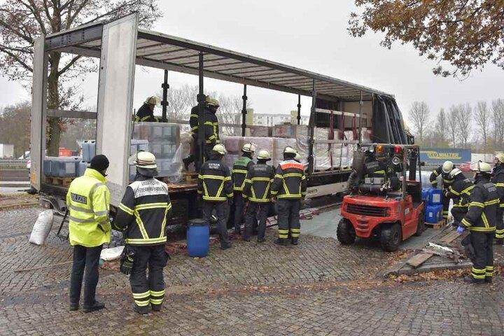Feuerwehrleute laden den Gefahrgut-Laster ab.