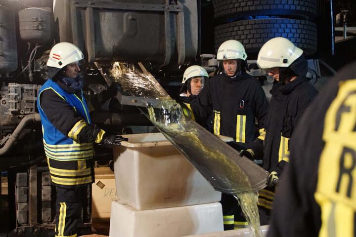 Feuerwehrleute füllen Diesel aus dem Tank des verunglückten Lastwagens um.