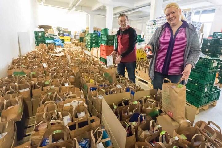 Tafel-Mitarbeiter Elena Kerbel (37) und Dieter Böhme (61) packen die Weihnachtstüten.