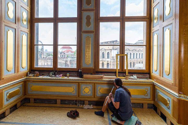 Ein Restaurator malt Goldverzierungen aus.