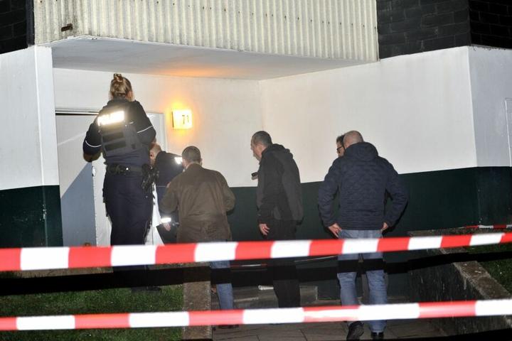 Beamte der Spurensicherung untersuchen den Eingang einer Wohnung.