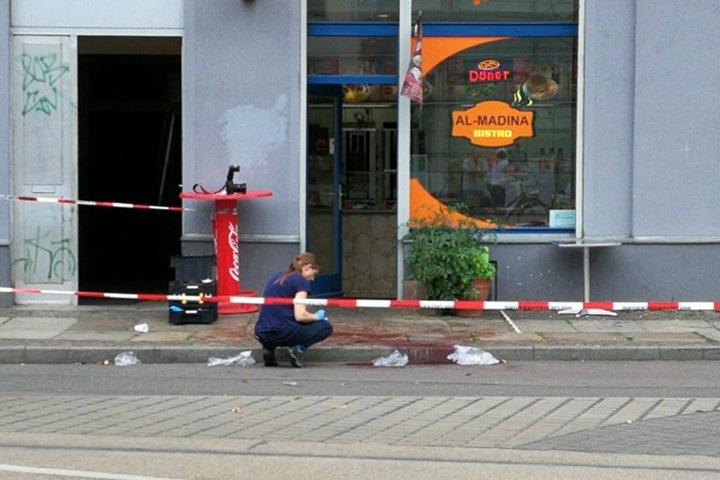 ine Beamtin der Spurensicherung dokumentierte am Tatort die Lage der Blutspuren.