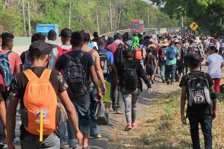 Migranten laufen eine Straße entlang.