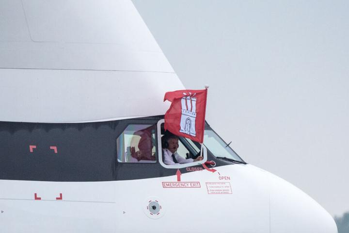 """Der Airbus-Pilot hält nach der ersten Landung des """"BelugaXL"""" in Hamburg eine Fahne der Stadt aus dem Cockpit-Fenster."""