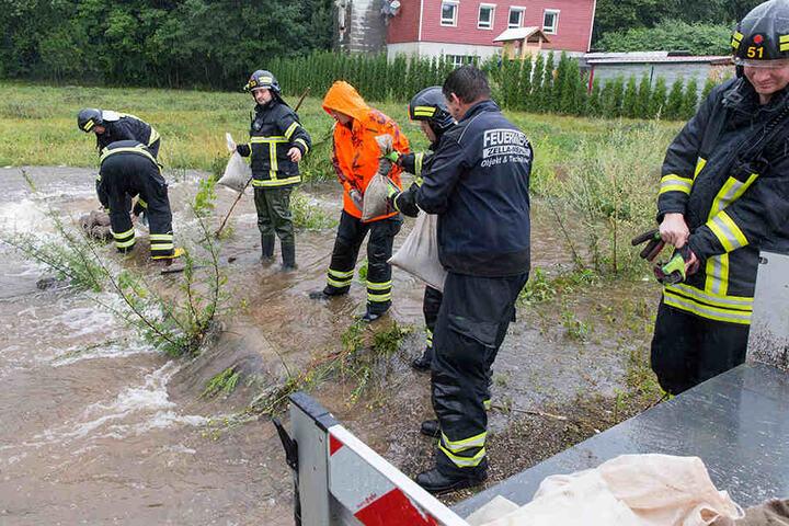 Feuerwehrleute schichten im Suhler Stadtteil Neundorf Sandsäcke auf.