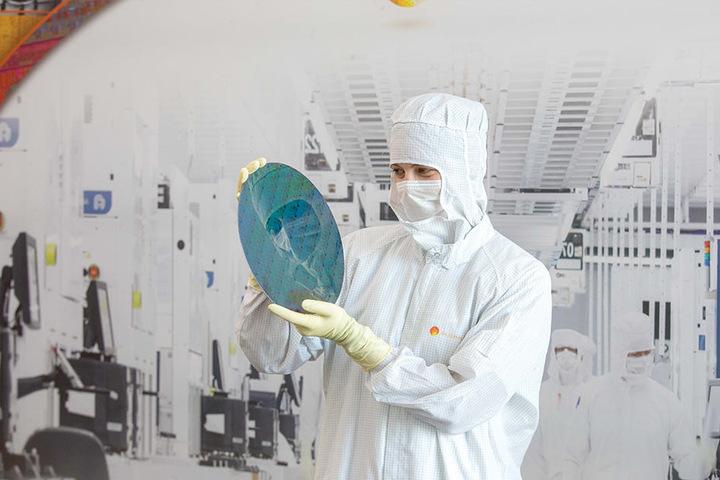 Mikrotechnologin-Azubi Lisa Marie Eisner zeigt einen Testwafer. 3500 Menschen arbeiten hier.