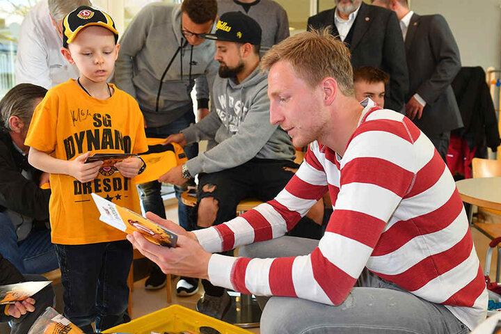 Dynamo-Kapitän Marco Hartmann  beschenkt den kleinen Lenny mit einem Dynamo-Buch.