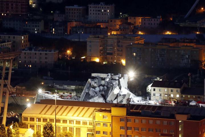 Rettungskräfte suchen nachts an der teilweise eingestürzten Autobahnbrücke nach Überlebenden während Scheinwerfer den Bereich ausleuchten.