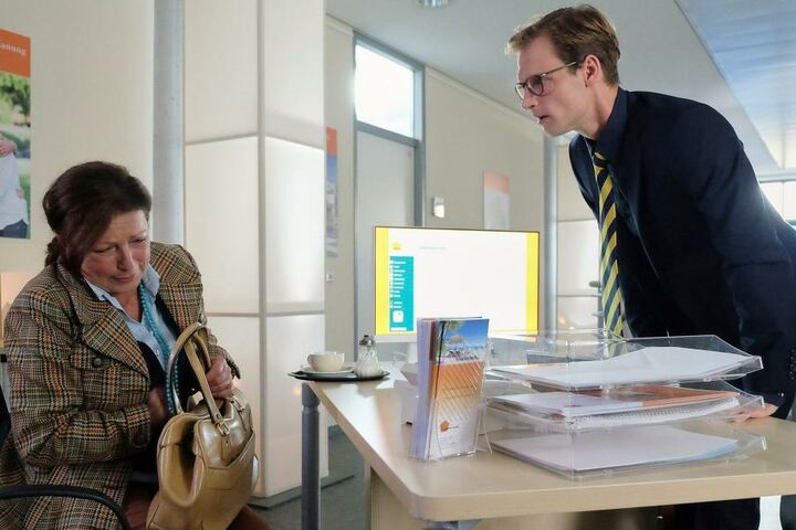Beim Gespräch mit ihrem Bankberater Nikolaus Habermann (r.) kollabiert Brigitte Felbers, nachdem sie erfährt, dass sie durch ein längst vergessenes Dauerlos eine hohe Summe gewonnen habe.
