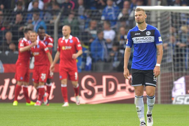 Arminias Florian Hartherz ist frustriert - im Hintergrund feiern die Duisburger ihren verdienten 4:0-Sieg.