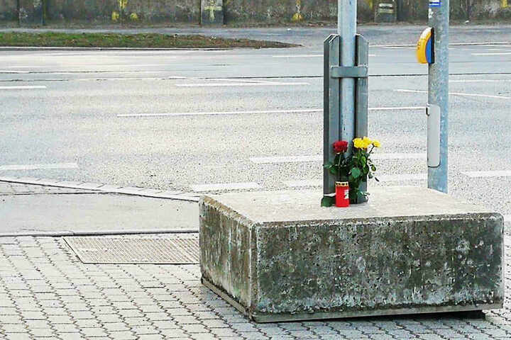 Rosen und eine Kerze erinnern an den tragischen Unfall.