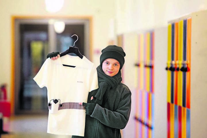 Kreuzchor-Tenor Lukas Neumann (16) zeigt es: Unter ihrer Winterkleidung tragen die Sänger beheizbare Unterwäsche.