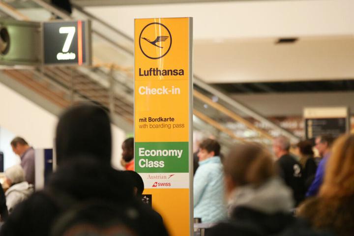 Flüggäste stehen neben einer Check-in-Säule der Lufthansa.