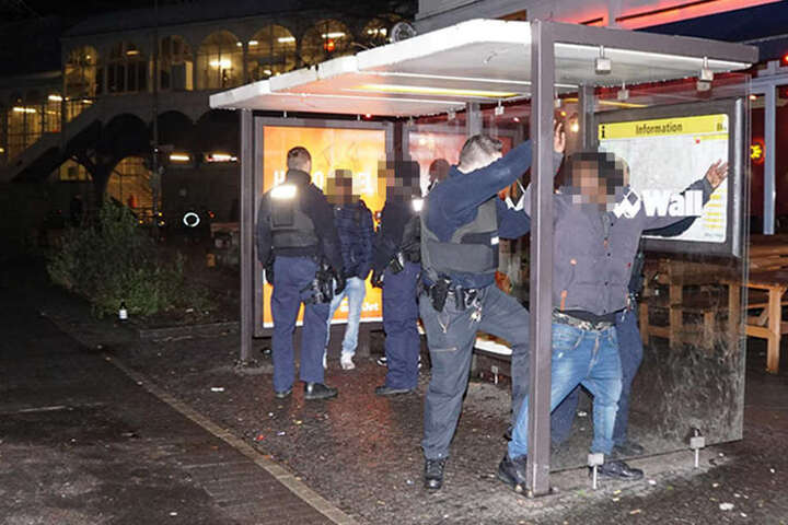 An einer angrenzenden Bushaltestelle kontrollieren Beamte eine involvierte Personengruppe.