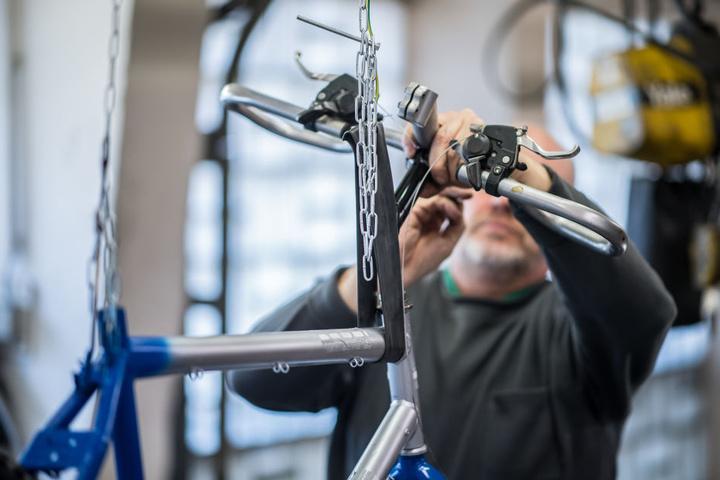 Der 58-jährige Häftling Uwe steht in der Fahrradwerkstatt der Abteilung für lebensältere Inhaftierte in der JVA Bielefeld-Senne und repariert ein Fahrrad.