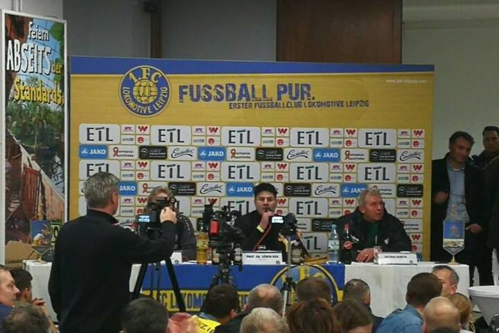 Unfreiwillige Bierdusche: BSG-Trainer Dietmar Demuth (re.) sitzt nach dem Becherwurf mit nassen Klamotten in der Pressekonferenz.