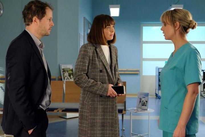 Plötzlich taucht Sina Wolter (M.), Claras Mutter auf. Als sie erfährt, dass ihr Kind doch operiert wird, rastet sie aus. Ihr Ex-Mann Tom (l.) hatte ihr Fax gefälscht, der OP darin zugestimmt.