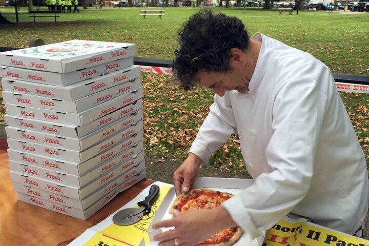 Der Pizzabäcker Teo Catino schneidet Pizza in London. Catino verschenkte Pizza und Wasser um sich bei den Rettungs- und Sicherheitskräften zu bedanken.