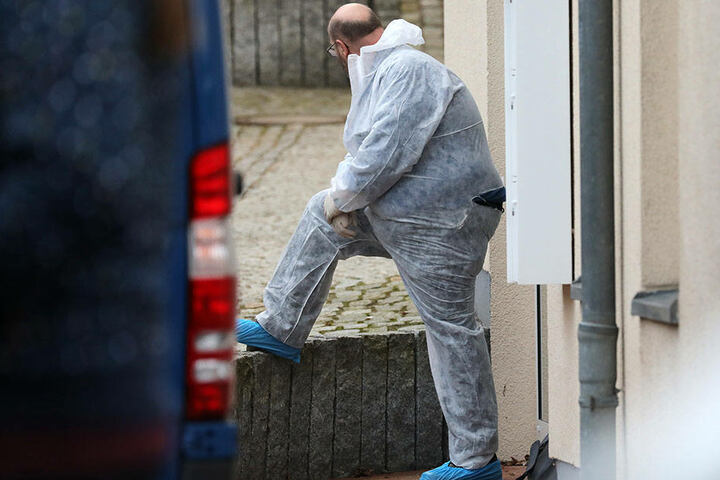 Ein Polizist in einem Overall steht vor dem Haus, in dem sich eine Anwaltskanzlei befindet, in der eine Frau erschossen wurde.