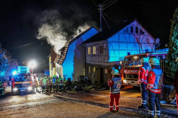 Einsatzkräfte vor dem brennenden Haus.