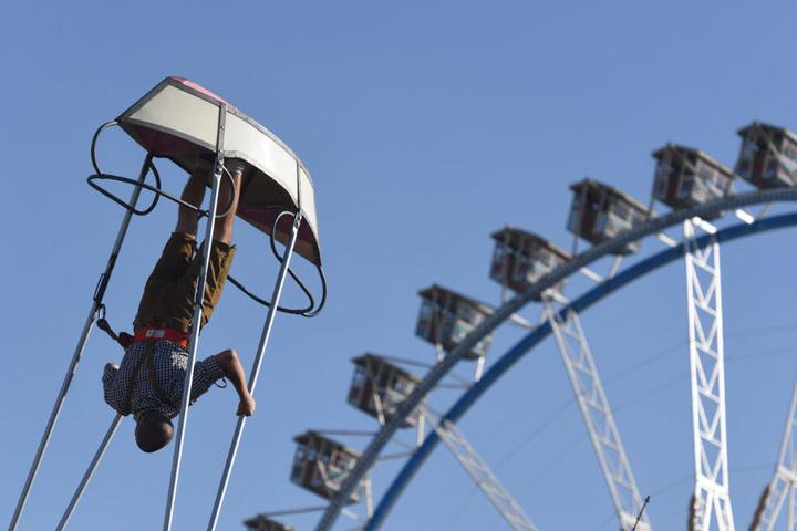 Ein Wiesnbesucher überschlägt sich in einer Schiffschaukel auf dem Oktoberfest vor dem Riesenrad.