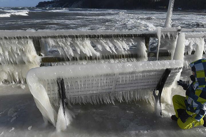 Auf einer Bank auf der Seebrücke hat sich ein Eispanzer aus zahlreichen Eiszapfen gebildet.