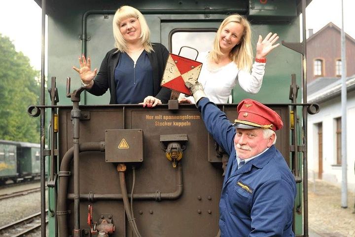 Mit der Fichtelbergbahn beim Fotoshooting um die Wette lächeln: Heidi Glaser (28), Anke Neubert (39) und Fahrdienstleiter Uwe Schulze (49, v.l.) zeigen schon mal, wie das aussehen könnte.