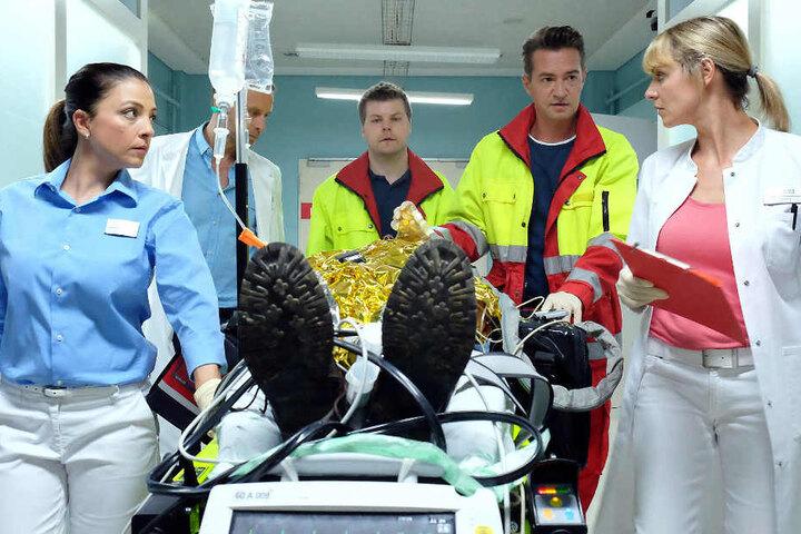 Der Notarzt (Markus Neumann, 2. v. r.) bringt ein Unfallopfer in die Sachsenklinik, das schwerste Brandverletzungen hat. Dr. Lea Peters, Dr. Kai Hoffmann (Julian Weigend, 2. v. l.) und Oberschwester Arzu müssen schnellstens reagieren. Der Patient schwebt
