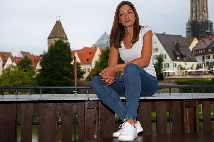 Mesale Tolu sitzt auf einem Geländer vor der Ulmer Altstadt.