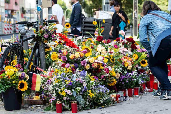 Mit Blumen und Kerzen gedenken Menschen der Opfer des Verkehrsunfalls.